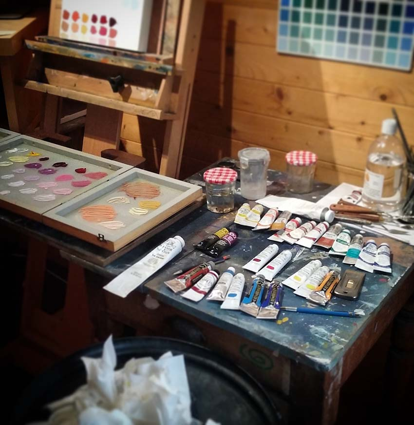 Art studio with tubes of paint on a palette